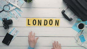 Top view time lapse hands laying on white desk word `LONDON` decorated with travel items stock video