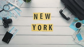 Top view time lapse hands laying on white desk word `NEW YORK` decorated with travel items stock footage
