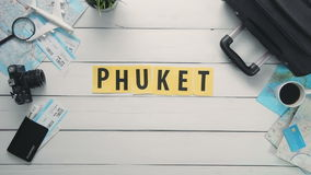 Top view time lapse hands laying on white desk word `PHUKET` decorated with travel items stock video footage