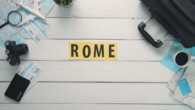 Top view time lapse hands laying on white desk word `ROME` decorated with travel items stock video footage