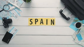 Top view time lapse hands laying on white desk word `SPAIN` decorated with travel items stock video footage