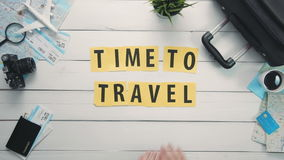 Top view time lapse hands laying on white desk word `TIME TO TRAVEL` decorated with travel items stock video footage