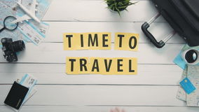 Top view time lapse hands laying on white desk word `TIME TO TRAVEL` decorated with travel items stock video