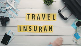 Top view time lapse hands laying on white desk word `TRAVEL INSURANCE` decorated with travel items stock video footage