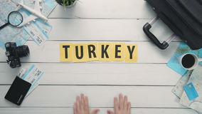 Top view time lapse hands laying on white desk word `TURKEY` decorated with travel items stock footage