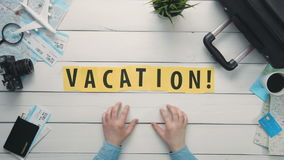 Top view time lapse hands laying on white desk word `VACATION` decorated with travel items stock video