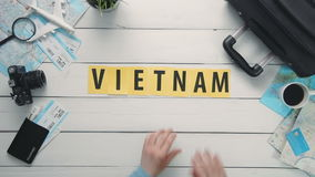 Top view time lapse hands laying on white desk word `VIETNAM` decorated with travel items stock footage