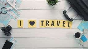 Top view time lapse hands laying on white desk words `I LOVE TRAVEL` decorated with travel items stock footage