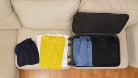 Top view timelapse packing clothes into a suitcase. Top view timelapse of packing clothes into a suitcase stock video footage