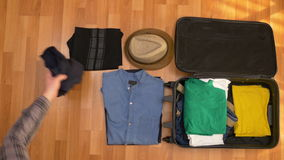 Top view timelapse of young man folding clothes in a travel bag. Top view timelapse of young man folding clothes in travel bag stock video footage