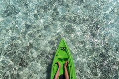 Tip of a kayak and man legs with clear blue water in the maldives as background stock photography