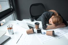 Weary female lying on desk. Top view tired businesswoman sleeping on table. Cups of coffee locating on it. Occupation and weariness concept Stock Photography