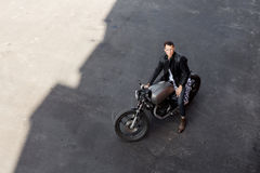 Top view to brutal man with cafe racer custom motorbike. Stock Image