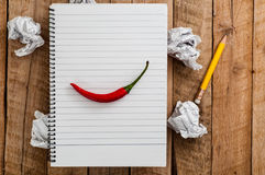 Top view to Empty lined paper page of notebook with chili pepper above crumpled paper balls and yellow pencil on plank wood table Stock Photos