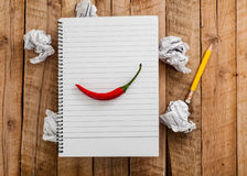 Top view to Empty lined paper page of notebook with chili pepper above crumpled paper balls and yellow pencil on plank wood table Stock Images