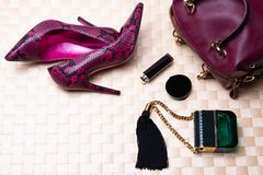 Top view to flat lay fashionable high heels, leather handbag, perfume and cosmetics on a bright table cloth stock photos