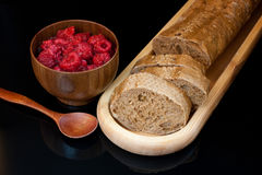 Top view to plate with  sliced bread, cup with raspberries and s. Top view to wooden plate with fresh sliced bread, cup with raspberries and spoon on black Stock Photos