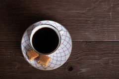 Top view to porcelain cup of coffee with toffee on old wooden ta Stock Image