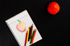 Top view to Sketch or red apple in lined page of notebook with colorful pencil and real red apple on dark wooden background Stock Photo