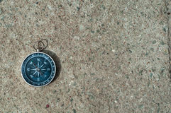 Top view to sone ground with one black Compass. Vintage compass on cement floor stock photo