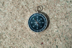 Top view to sone ground with one black Compass. Vintage compass on cement floor royalty free stock photos