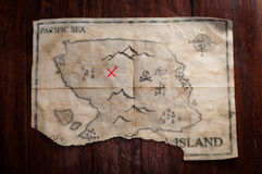 Top view to vintage fake crumpled treasure map on wooden table. Fake pirate handmade map with red cross as place of Treasure chest Stock Images
