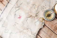 Top view to vintage fake treasure map with red cross and compass on wooden desk Royalty Free Stock Images