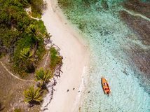 Top view of Tobago cays. Aerial drone view of Petit Tabac tropical island, turquoise Caribbean sea of Tobago cays, and a family with kids in St Vincent and stock photography