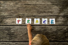 Top view of toddler girl touching the word Peace pinned on a tex Stock Photography