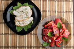 Top view on tomato salad and slices of baked chicken Stock Photography