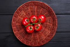 Top view of tomatoes in a basket. Ripe, juicy, colorful red tomatoes on a black background. stock photography
