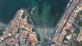 Top view of town beach, quay, houses of Cadaques. Straight down drone view of turquoise water of bay, beach, seaside promenade and white houses with tiled roofs stock video footage