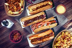 Top view on traditional american fast food. Hot dog with bacon and cheese on brown background around herbs and spices. stock photos