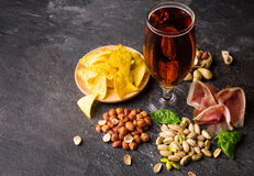 Top view of traditional snacks and dark beer on a gray background. Peanuts, pistachios, meat with a glass of beer. Cold. A view from above on different tasteful Royalty Free Stock Photo