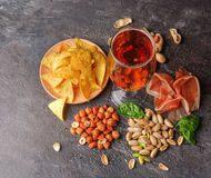 Top view of traditional snacks and dark beer on a table background. Peanuts, pistachios, meat with a glass of beer. Cold. A view from above on different tasteful Royalty Free Stock Photo
