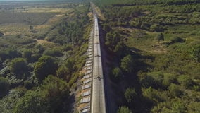 Top view of train and railway in the country, sunset. Train running over railway in the forest at sunset, aerial view stock footage