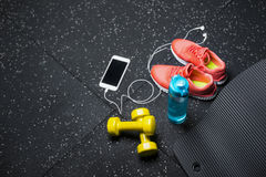 A top view of trainers, sports bottle, phone and dumbbells on a black background. Sports accessories. Copy space. A view from above of colorful training shoes Royalty Free Stock Photos