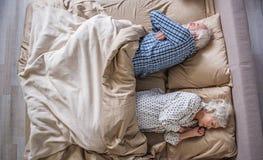 Calm senior couple having nap at home royalty free stock photography