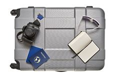 Some for tour journey. Top view of travel accessories lying on gray suitcase Royalty Free Stock Images