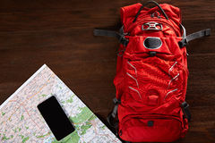 Top view of the travel backpack with map and telephone on the wooden background. Stock Photo