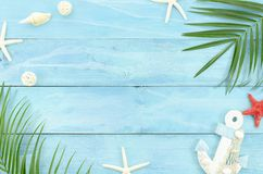 Top view travel concept banner framed summer beach and sea stuff, starfish, shells, anchor and palm tree branch leafs. Flat lay ocean theme on blue wooden stock photos