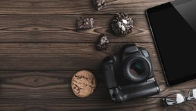 Top view travel concept with modern camera, digital tablet, eyeglasses and biscuits. Outfit of traveler on brown background with copy space stock photography