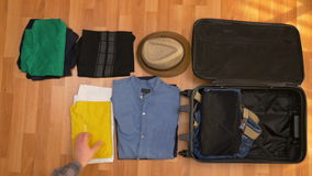 Top view travel concept of tourist man orderly packing his clothes into a suitcase stock footage