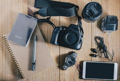 Top view of travel object : passport and gray pencil on brown notebook. and white mobilephone, earphone, black camera and two lens Royalty Free Stock Photography