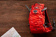 Top view of the travel orange backpack with map on the wooden background. Stock Photography