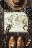 top view of travel setting with straw hat, map, shoes, compass, magnifying glass and photo cameras on dark royalty free stock photography