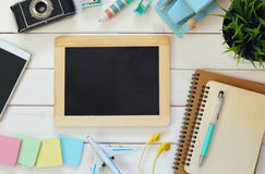 Top view of travel supplies next to blank blackboard Royalty Free Stock Photo