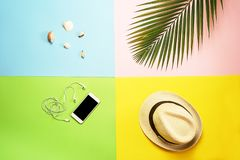 Top view traveler accessories layout: tropical palm leaf, white straw hat, mobile phone and headphones, seashells on colorful. Flat lay traveler accessories stock photo