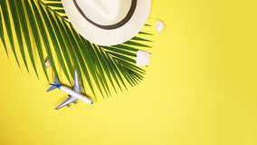 Flat lay traveler accessories: tropical palm leaf branches, white straw hat, airplane toy and seashells on yellow background with royalty free stock photos