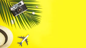 Flat lay traveler accessories tropical palm leaf, white straw hat, airplane toy, retro camera and seashells on yellow colorful stock image